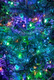 Елка с игрушками, гирляндами, мишурами лилово-сине-зеленого цвета. часть украшенной елки в качестве фона или обоев. вертикальная ориентация. мягкий фокус.