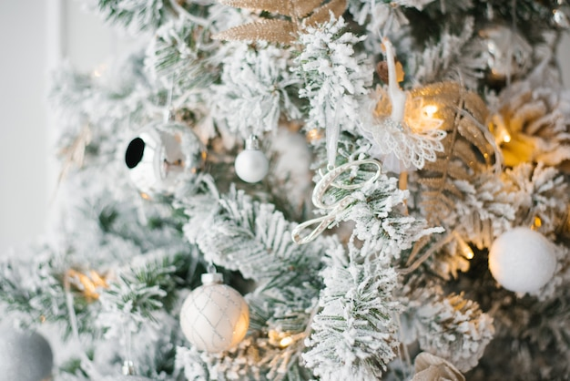 Christmas tree with white, silver and gold toys and lights close-up