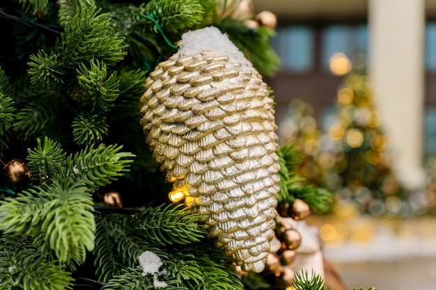 Christmas trees decorated with sparkling cones and garland with lights on