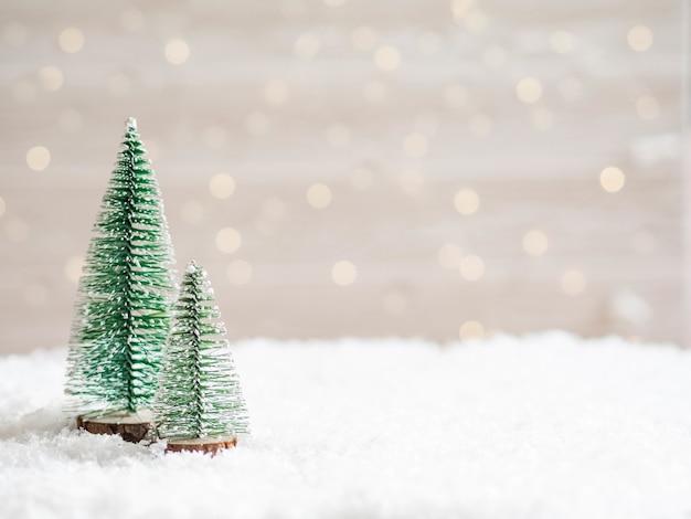 Новогодние елки на переднем плане в искусственном снегу с светящейся гирляндой. скопируйте пространство.