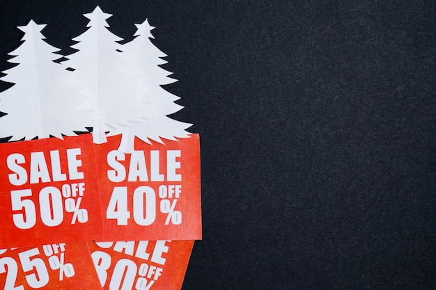 Christmas trees made of white paper on red plates with discounts