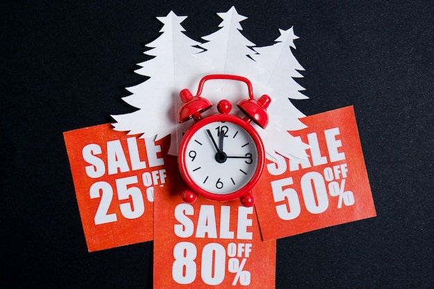 Christmas trees made of white paper on red stickers with discounts and a vintage clock