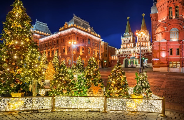 Christmas trees on manezhnaya square in moscow near the resurrection gate and christmas-tree decorations in night-time lighting