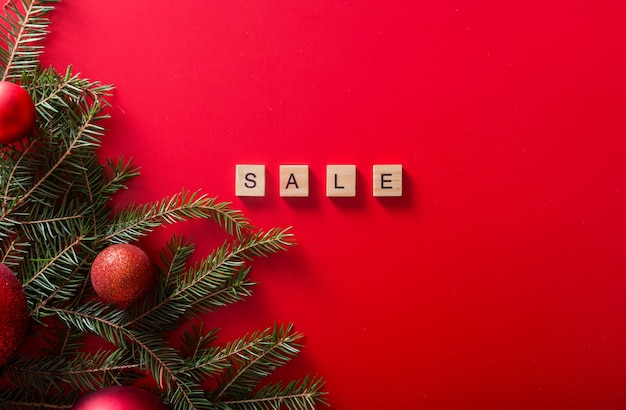 Christmas trees with red balls and the word sale made of wooden letters