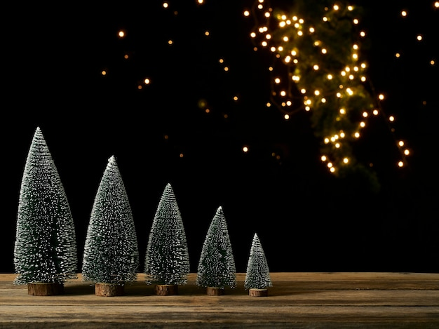 Christmas trees with snow on wooden table against dark background, bokeh effect, space for text