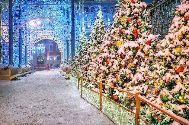 Елки с игрушками под снегом возле здания мэрии москвы накануне праздника при вечерней иллюминации