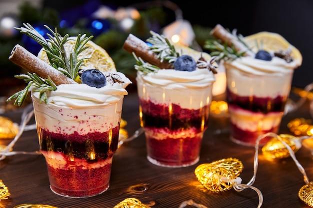 Рождественские мелочи в чашках в качестве десерта, украшенные свежей черникой и палочкой ванили