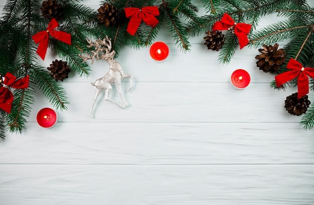 キャンドルと弓のあるクリスマスの小枝