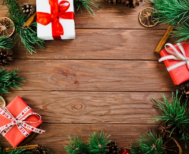 Christmas twigs and boxes on wooden board