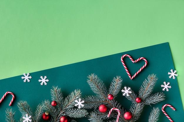 テキストスペースとクリスマスのツートンカラーの緑の背景。装飾が施されたモミの小枝の上のパノラマビュー。