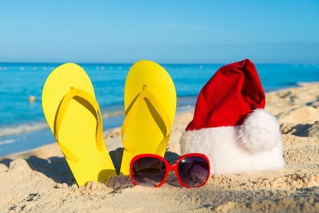 Christmas vacation at sea. happy  new year holidays. santa hat, sandals, sunglasses on sandy beach