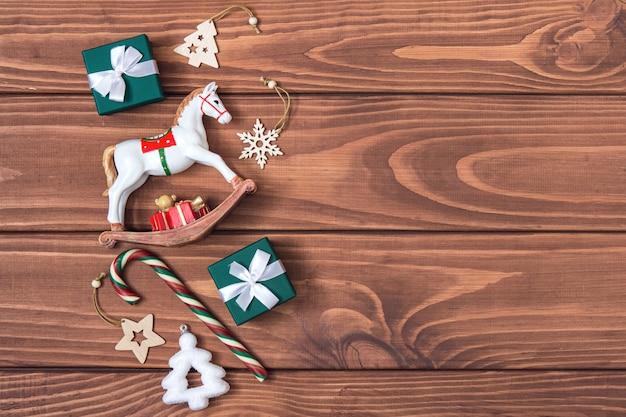 크리스마스 빈티지 프레임입니다. 어두운 나무 배경에 크리스마스 장난감, 과자, 사탕, 선물 상자. 복고풍 크리스마스 카드를 비웃습니다. 복사 공간, 평평한 위치.