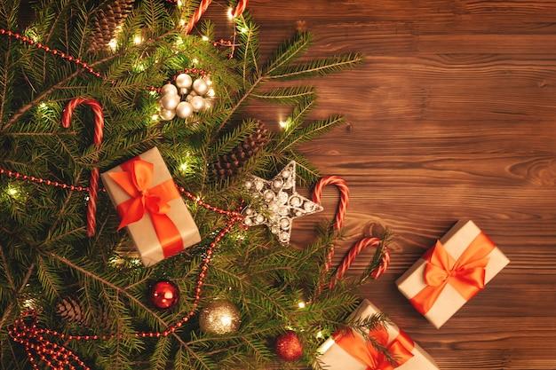 Рождественская стена с копией пространства. празднично оформленные еловые ветки на темно-коричневой деревянной доске. подарочные коробки и леденцы из тростника.
