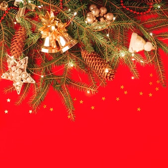 コピースペースのあるクリスマスの壁。赤い四角いバナーにお祝いに飾られたトウヒの枝。