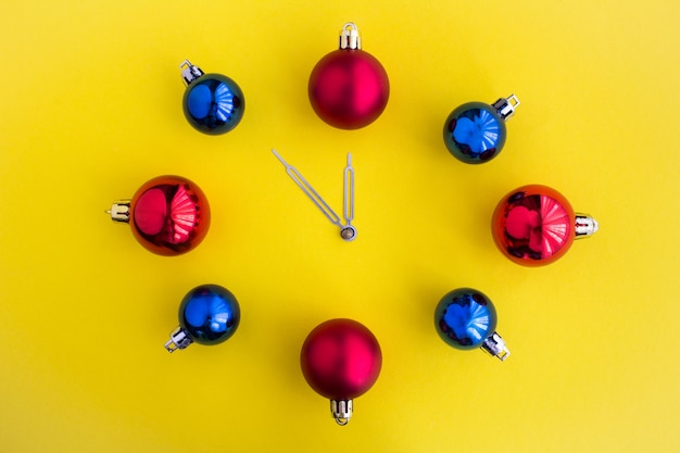 노란색 표면의 중앙에 밝은 공에서 크리스마스 시계. 평면도. 공간을 복사하십시오.