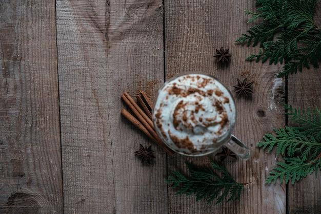 크리스마스 휘핑 크림 핫 코카, 계피, 아니스 별, 나무 배경 위에 있는 투자 가지, 크리스마스 및 새해 음료