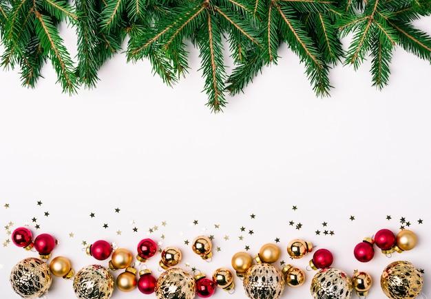 크리스마스 흰색 배경입니다. 금색과 분홍색 공 및 침엽수 가지 테두리