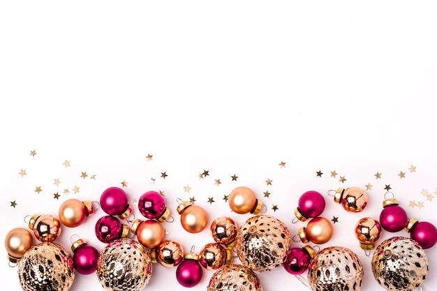 Рождественский белый фон. сияющие золотые и розовые шары и граница конфетти