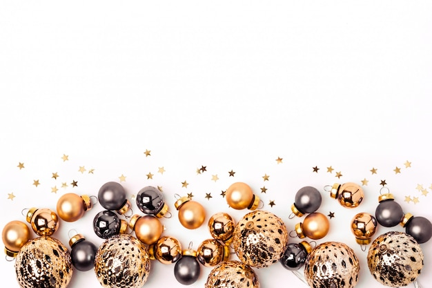 Christmas white background. shining gold and gray balls and confetti border