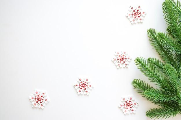 モミの枝と白と赤の雪片とクリスマスの白い背景。