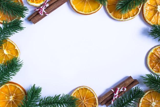 Рождественский белый фон с местом для текста, еловыми ветками по краям, сушеными апельсинами и палочками корицы