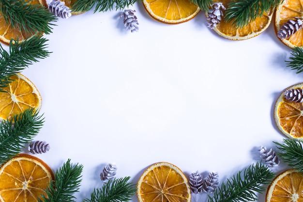 テキストの場所、端の周りのモミの枝と乾燥したオレンジと雪に覆われた円錐形のクリスマスの白い背景
