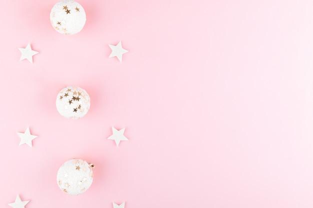 クリスマスの白いボール、スタイリッシュなピンクのテーブルトップビューのスパンコール。ファッションの背景。フラットレイお祭りエレガントな構成。