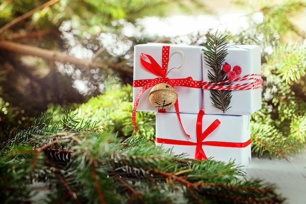クリスマスの白い箱は赤いリボンと金属のジングルベルを飾りました