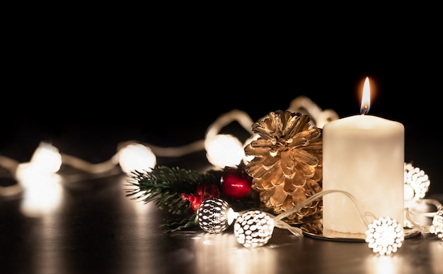 Christmas white candle with golden pine cone,mistletoe and light string glowing