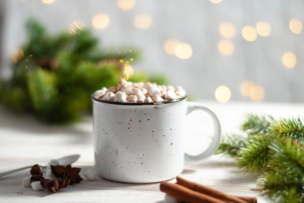 Рождественская белая чашка с горячим шоколадом и зефиром с корицей и еловыми ветками елки
