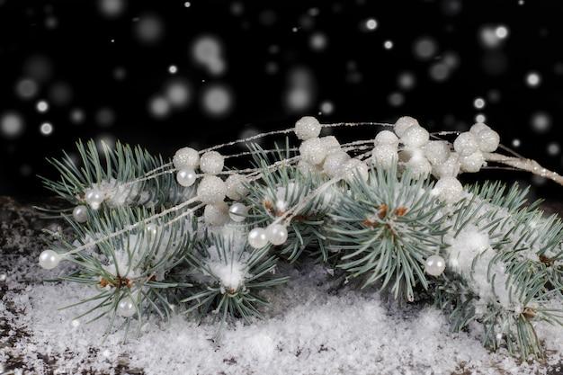 背景のクリスマスツリーの枝にクリスマスの白い装飾