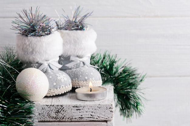 Рождественские белые украшения с игрушечными сапогами на деревенском столе
