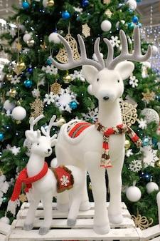 Christmas white deer and little deer near the christmas tree. deer rudolf. christmas composition