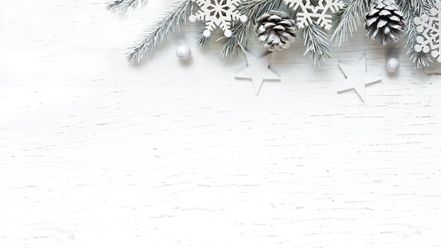 Christmas white fir tree branches pine cones and decorations on white wooden background. winter background with copy space.