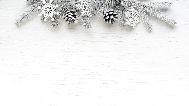 Christmas white fir tree branches pine cones and snowflakes on white wooden background. winter background with copy space.