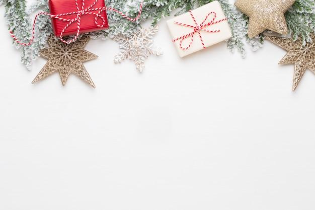 Рождественские белые еловые ветви с украшениями золотых звезд.