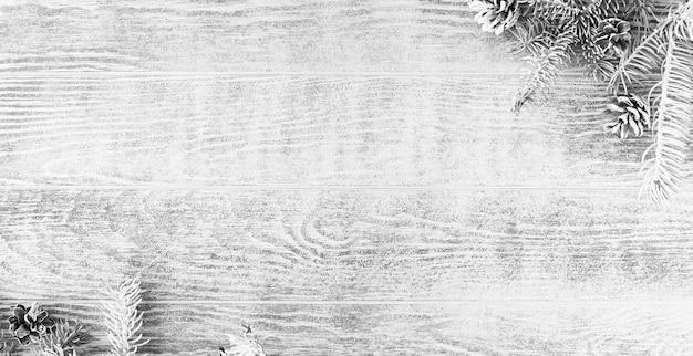 雪に覆われた松ぼっくりとクリスマスの白いモミの木の枝。木製テーブルのクリスマス作曲、コピースペース付きパノラマバナー