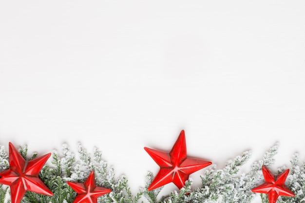 Рождественские белые еловые ветви с украшениями звезд.