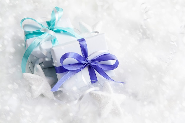 Christmas white gift boxes in snow. winter xmas holiday theme. merry christmas and happy holidays greeting card.