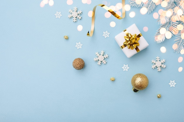 Christmas white gift with gold bow and ornaments on blue background, top view. merry christmas and happy holidays greeting card.