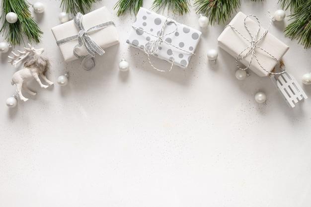 Рождественские белые подарки, сани, олени, вечнозеленые ветви на белом. плоская планировка.