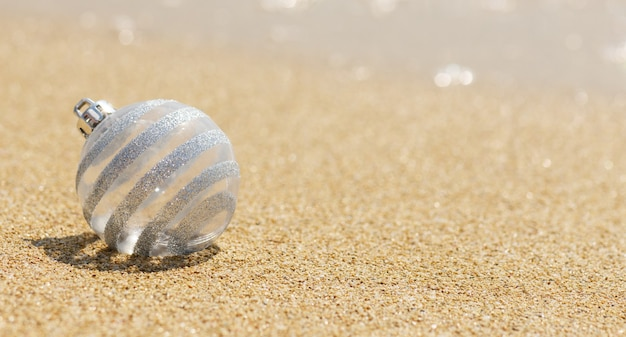 Christmas white glitter ball on the tropical beach near ocean, merry christmas and happy new year