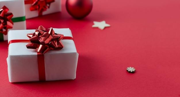 赤いリボンとジンジャーブレッドのクッキーで結ばれた赤い背景の上のクリスマスの白い手作りギフトボックス