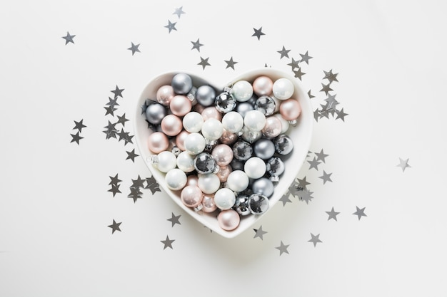 Christmas white, pink, grey silver balls in shape of heart on pink background decorated confetti stars xmas concept.