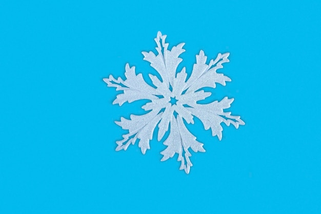 Christmas white snowflake on a blue background close-up. background concept for christmas and new year with copy space.