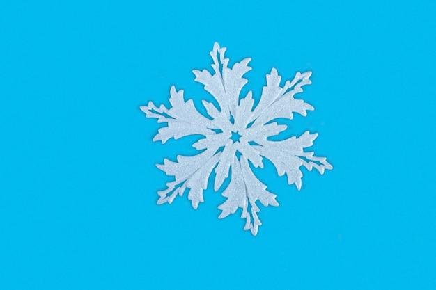 青い背景のクローズアップのクリスマスの白い雪の結晶。コピースペースとクリスマスと新年の背景コンセプト。