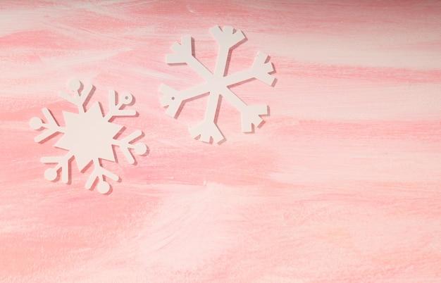 분홍색 배경에 크리스마스 하얀 눈송이 장식입니다. 분홍색 표면에 하얀 눈송이입니다.