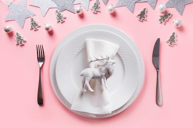 Christmas white table setting on pink.