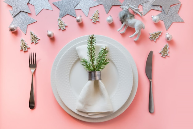 Christmas white winter table setting with reindeer on pastel pink background