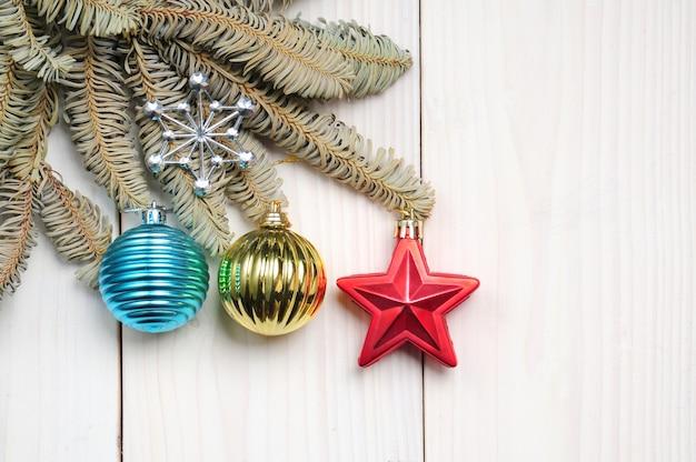 クリスマスツリーの枝やおもちゃとクリスマスの白い木の背景